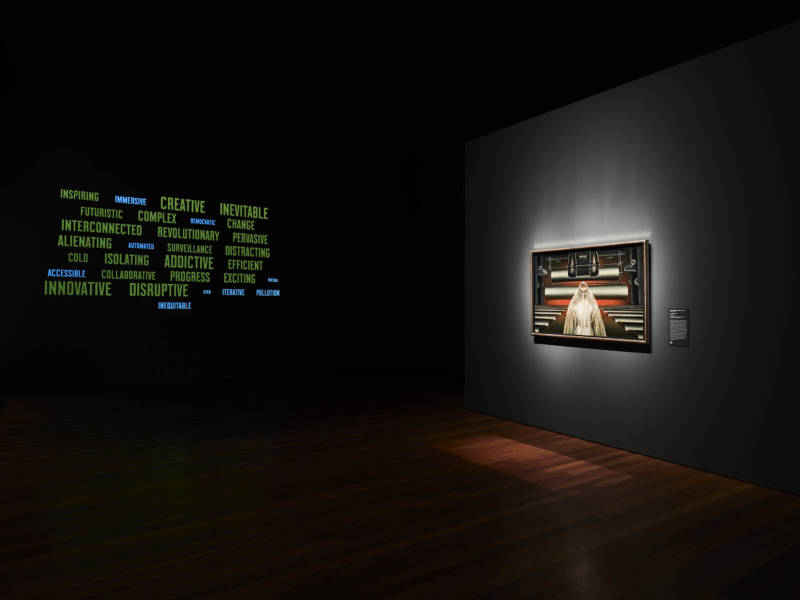 """Clarence Holbrook Carter's """"War Bride"""" (1940) sits in striking contrast opposite a positive word cloud featuring adjectives describing technology. There's another, negative word cloud. Both are generated by the choices of people visiting the exhibition Cult of the Machine."""