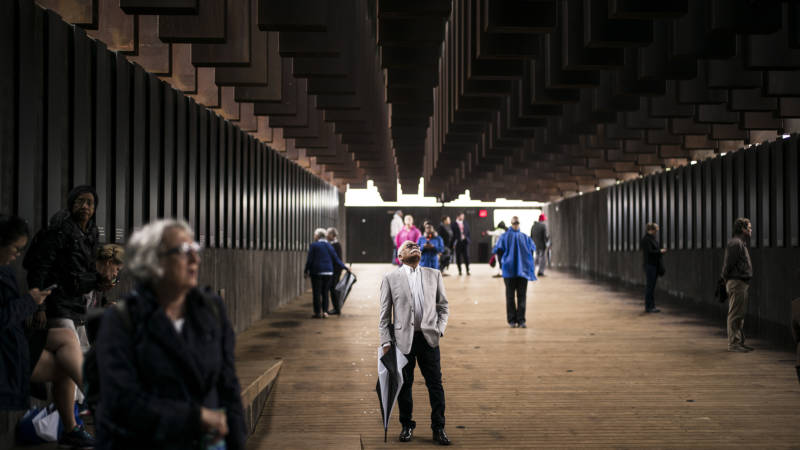 """Ed Sykes (center), 77, visits the National Memorial For Peace And Justice on April 26, 2018 in Montgomery, Alabama. Sykes, who has family in Mississippi, was distraught when he discovered his last name in the memorial, three months after finding it on separate memorial in Clay County, Mississippi. """"This is the second time I've seen the name Sykes as a hanging victim. What can I say?"""" Sykes, who now lives in San Francisco, plans to investigate the lynching of a possible relative at the Equal Justice Initiative headquarters in Montgomery before returning to California. The memorial is dedicated to the legacy of enslaved black people and those terrorized by lynching and Jim Crow segregation in America. Conceived by the Equal Justice Initiative, the physical environment is intended to foster reflection on America's history of racial inequality."""