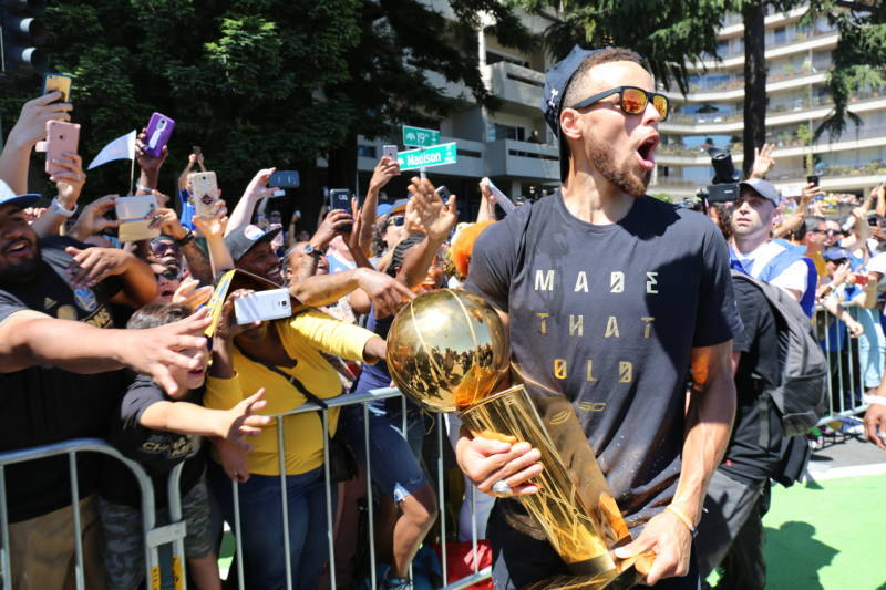 Stephen Curry brings the NBA Championship trophy to the people during the Warriors parade in Oakland on June 15, 2017.