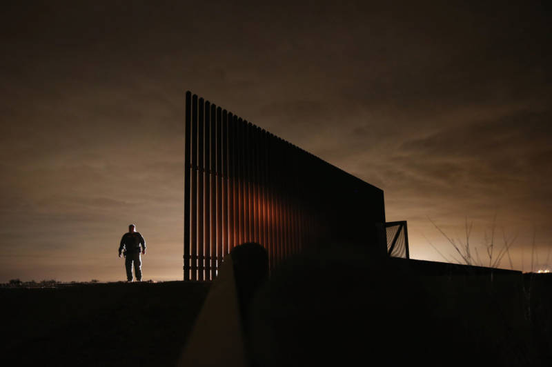 U.S. Border Patrol agent Sal De Leon stands near a section of the U.S.- Mexico border fence while stopping on patrol in 2013 in La Joya, Texas.