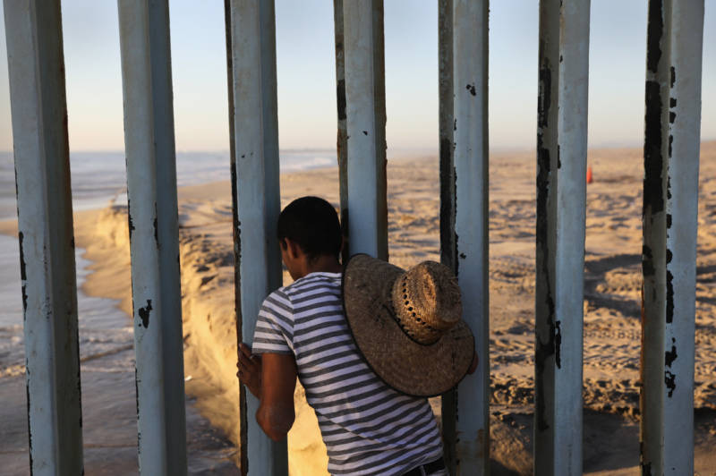 A man looks through the U.S.-Mexico border fence into the United States from Tijuana, Mexico, in 2016. Friendship Park on the border is one of the few places on the 2,000-mile border where separated families are allowed to meet.
