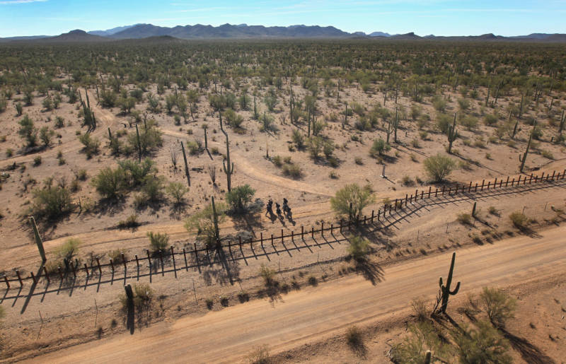 A group of young men walk along the Mexican side of the border fence in a remote area of the Sonoran Desert in 2010 on the Tohono O'odham Reservationin Arizona