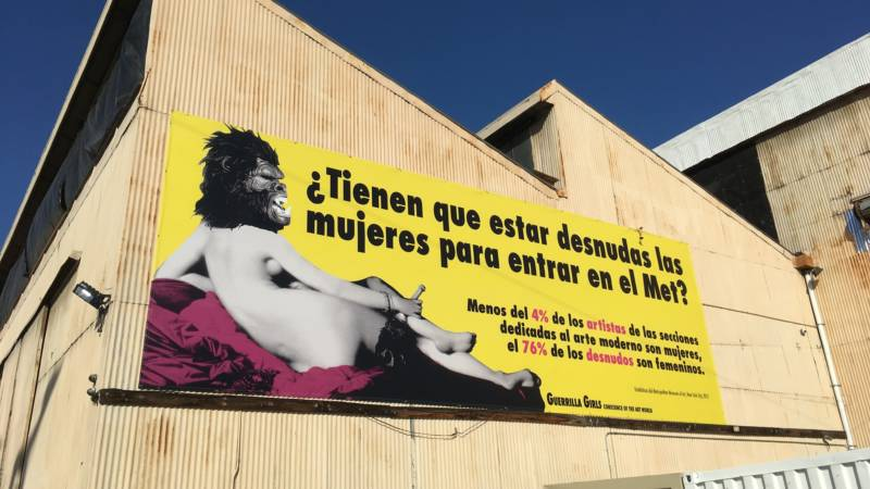 "'Beyond the Streets' boasts one of the Guerrilla Girls' most well-known billboards — in Spanish. It translates to ""Do women have to be naked to get into the Met? Less than 4 percent of the artists in the modern art sections are women, but 76 percent of the nudes are female."""