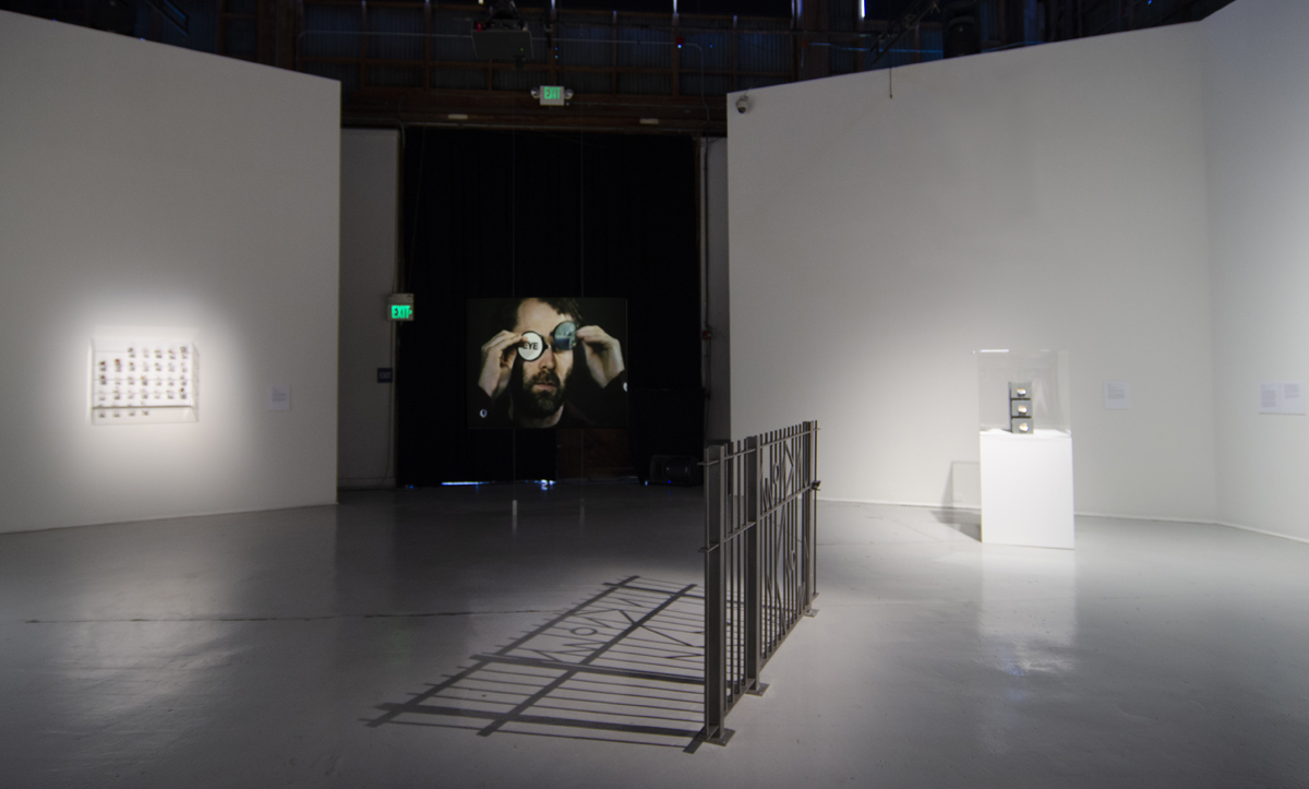 Installation view of 'Something (you can't see, on the other side, of a wall from this side) casts a shadow,' with video by Stuart Sherman in the center.