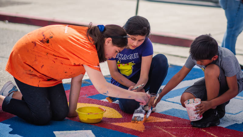 Students help paint a mural near the ASCEND School in Oakland.
