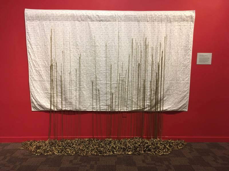 """Mending Gold: When Will It Be Enough?"" 2017 by Brooke Harris-Stevens. Each thread anchored into the brass casings signifies the number of mass shootings in an American city."