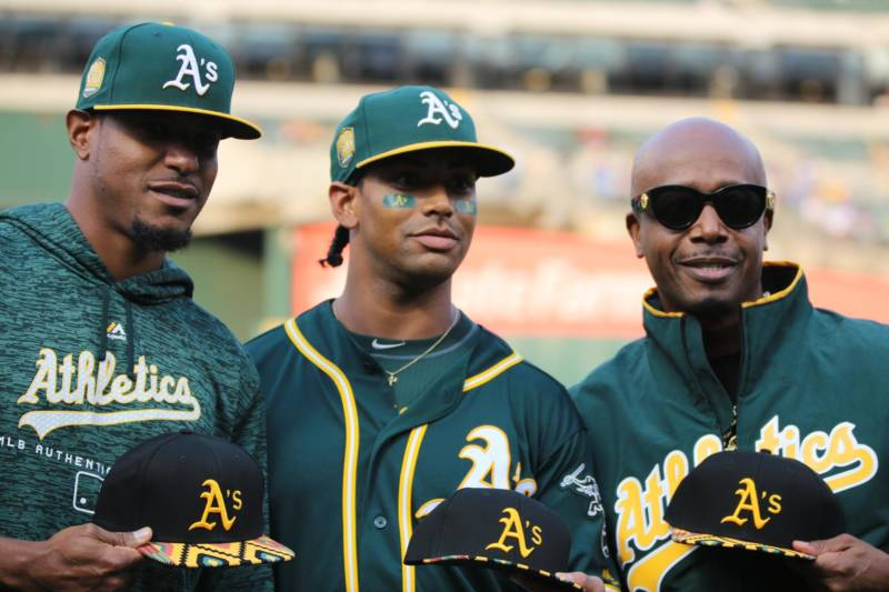 Edwin Jackson and Khris Davis show off their African American Heritage Night baseball caps with MC Hammer (L–R) at the Coliseum.