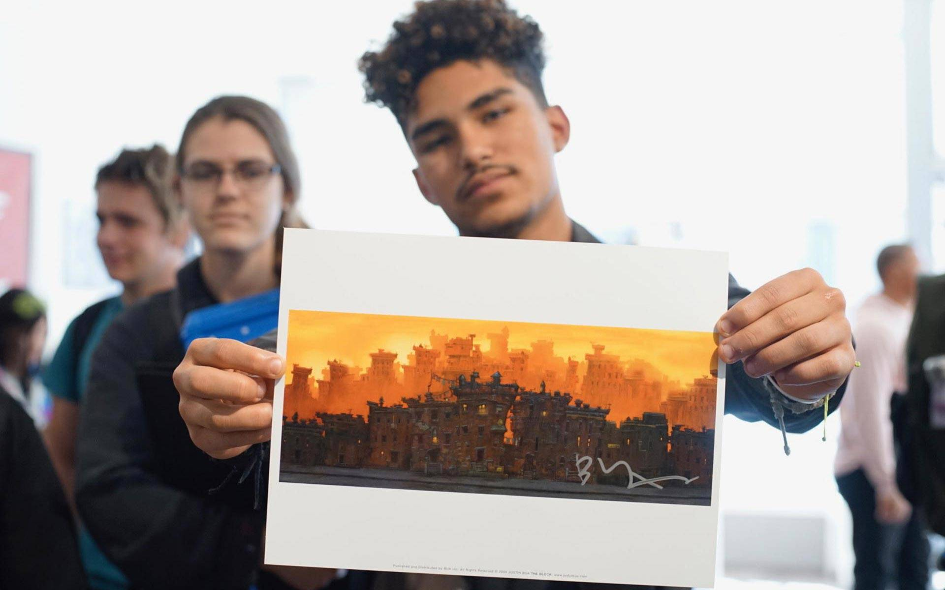 A student from Oakland School for the Arts holds up a print by artist Justin Bua. The artist appeared at SoleSpace in downtown Oakland for a talk with students. Pendarvis Harshaw