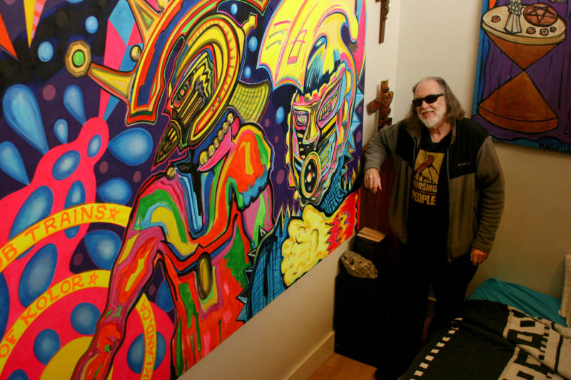 Robert Gill shows off his latest painting inside his East Oakland apartment.