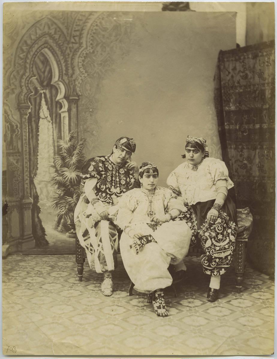 Three seated women in Tunisian trousers.