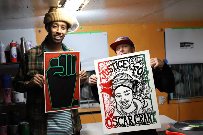 Kalleb Arefaine and Jon-Paul Bail printed thousands of anti-police brutality posters over the past decade. Bail (right) holds a poster he created with Aambr Newsom in 2012.