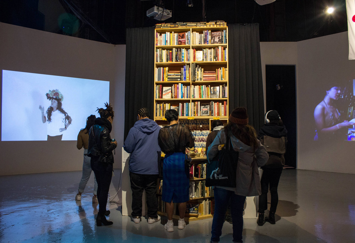 Opening reception visitors in front of Scott Ortega-Nanos' 'Pasyon: a Heuristic Pedagogy,' 2018.