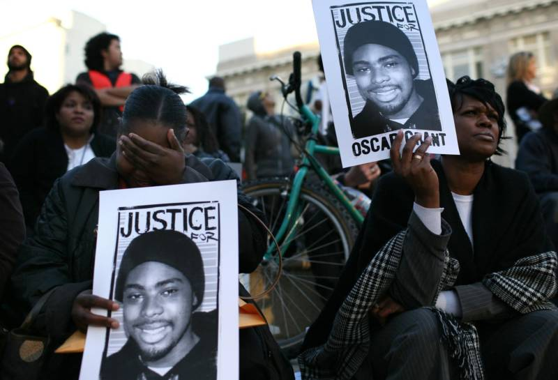 Protestors carry signs with a picture of slain 22-year-old Oscar Grant III during a demonstration at Oakland City Hall Jan. 14, 2009 in Oakland.