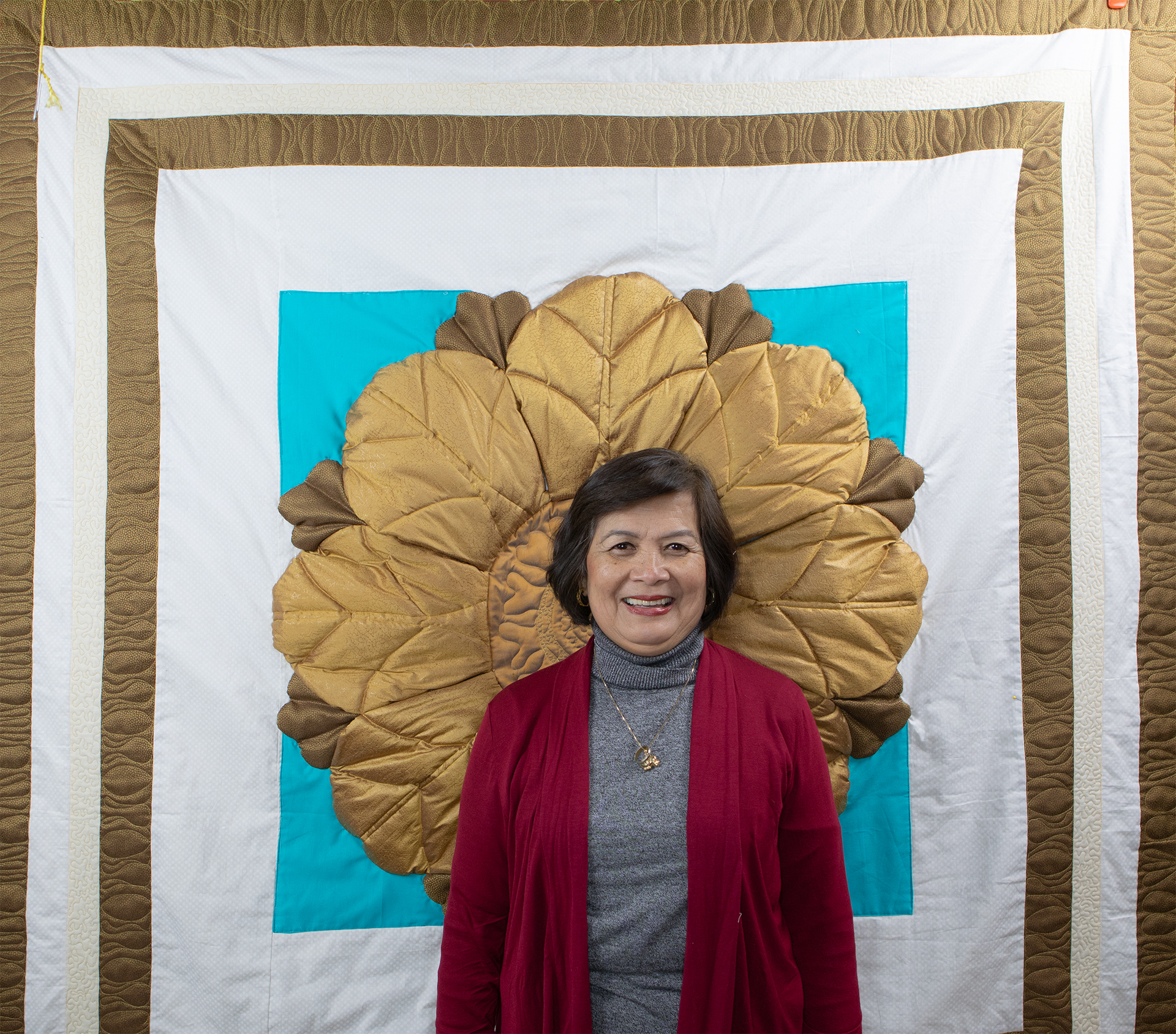 May Gaspay posing in front of a quilted version of a ceiling ornament from the Opera Building.