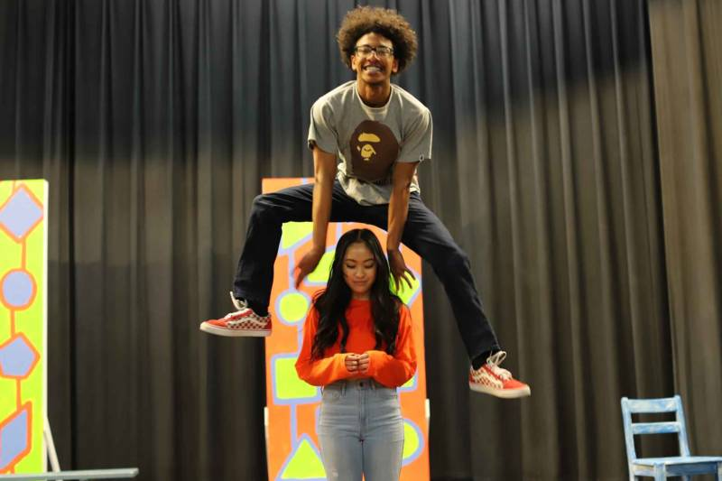 Trevahn Srey leaps over Trinity Chau during rehearsals for 'Hairspray' at Oakland High School.