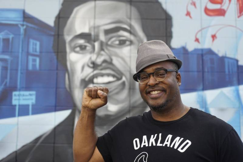 Artist Refa One with his mural honoring Huey Newton at 14th and Peralta in West Oakland.