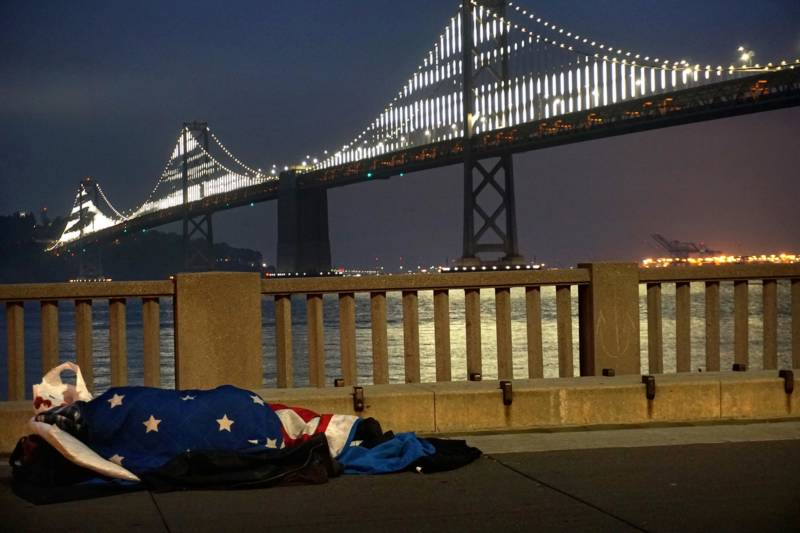 A homeless man lays wrapped in an American flag in front of the gleaming San Francisco Bay Bridge.