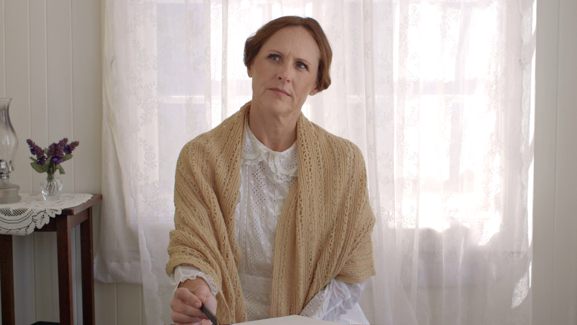 Emily (Molly Shannon) thinking at her desk in 'Wild Nights with Emily.'