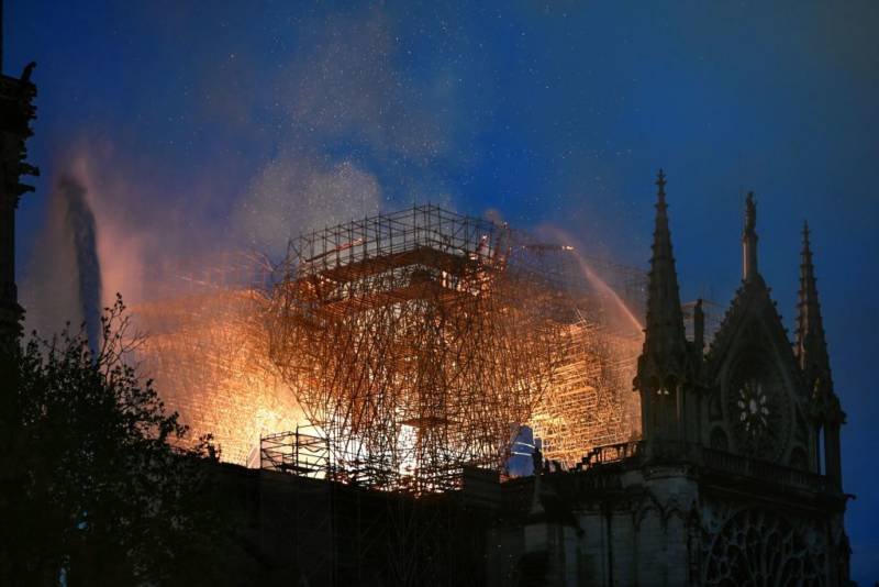 Flames are doused through the scaffolding erected on the roof of the Notre-Dame de Paris Cathedral after a fire broke out on April 15, 2019, in the French capital Paris.