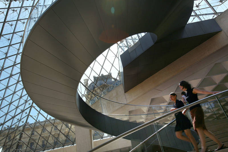 Visitors walk inside the Pyramid, the entrance of the Louvre Museum, on June 17, 2009 in Paris.