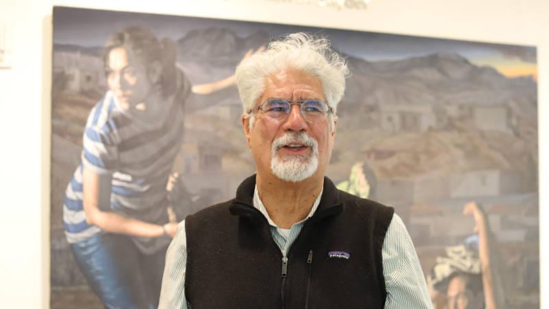 "Curator David J. de la Torre stands in front of ""La Guia (The Guide)"" by Rigoberto Gonzalez in the Jewish Community Center of San Francisco."