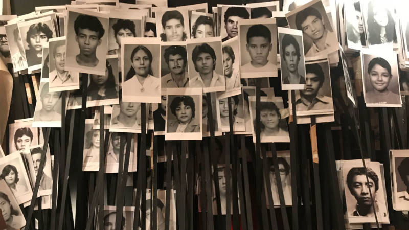 """Victor Cartagena's """"Expulsion/Implosion."""" which incorporates Salvadoran passport photos from the 1980s, anchors the borders-themed exhibition at the Jewish Community Center of San Francisco."""