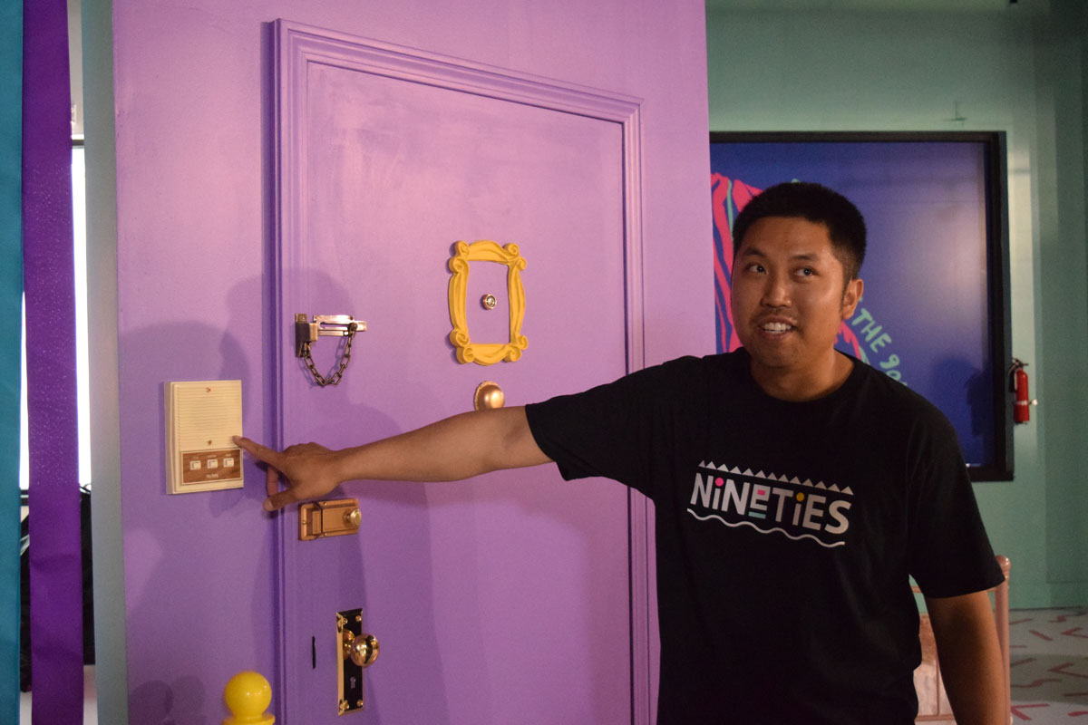 Co-organizer Ky Truong pointing out the intercom beside a replica 'Friends' apartment door.
