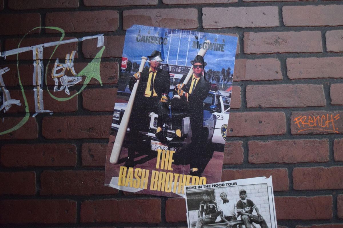 "Posters and flyers on a faux-brick wall at ""The 90's Experience."""