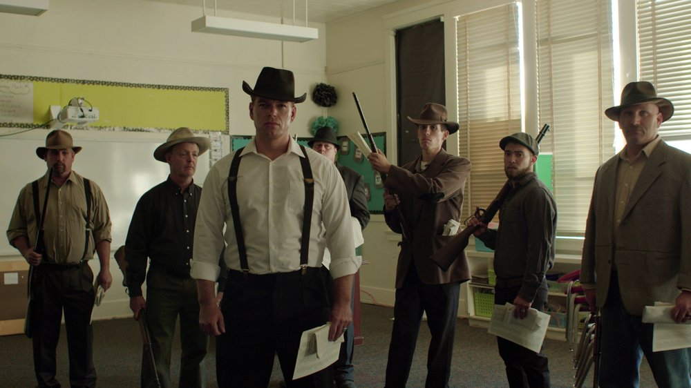 "Town residents dressed in period costume stand in a modern day classroom in ""Bisbee '17,"" as they re-enact the deputizing of a private police force that broke up a brewing strike at a copper mine on July 12, 1917."