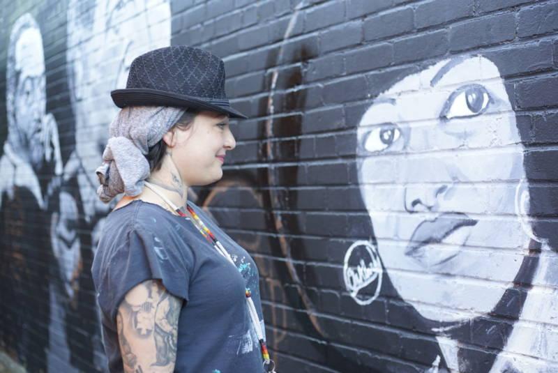 Mujer Muralista admiring her work.