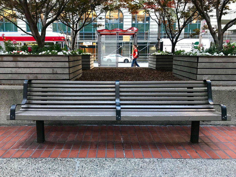 A park bench with armrests off Market Street near Embarcadero BART Station. Hostile design is motivated by preventing a person or group from taking specific actions.