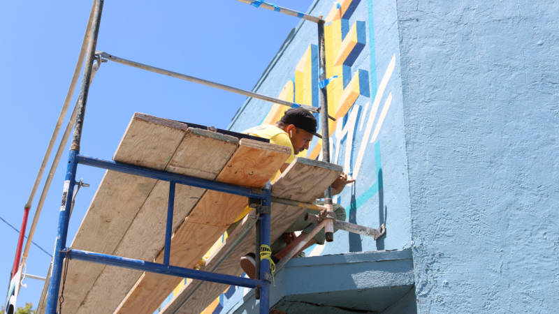 "Critical Resistance commissioned muralist-activists Leslie ""Dime"" Lopez and Dominic ""Treat U Nice"" Villeda (pictured) to paint the building."