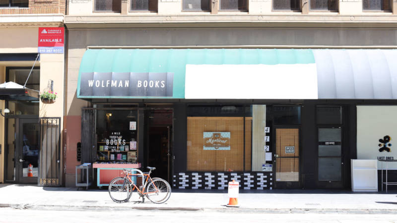 Justin Carder of E.M. Wolfman General Interest Small Bookstore is among the 13th Street merchants skeptical of the incoming plaza.