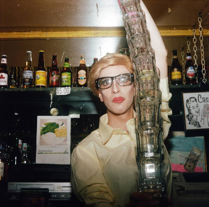 Mandy Coco dressed as Myles Cooper cleaning up glasses on a busy night at High Fantasy, at Aunt Charlie's in the Tenderloin.