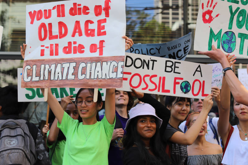 "Demonstrators at the Climate Strike in San Francisco on Sept. 20, 2019. Teenage girls hold signs that say ""You'll die of old age, I'll die of climate change"" and ""Don't be a fossil fool."""