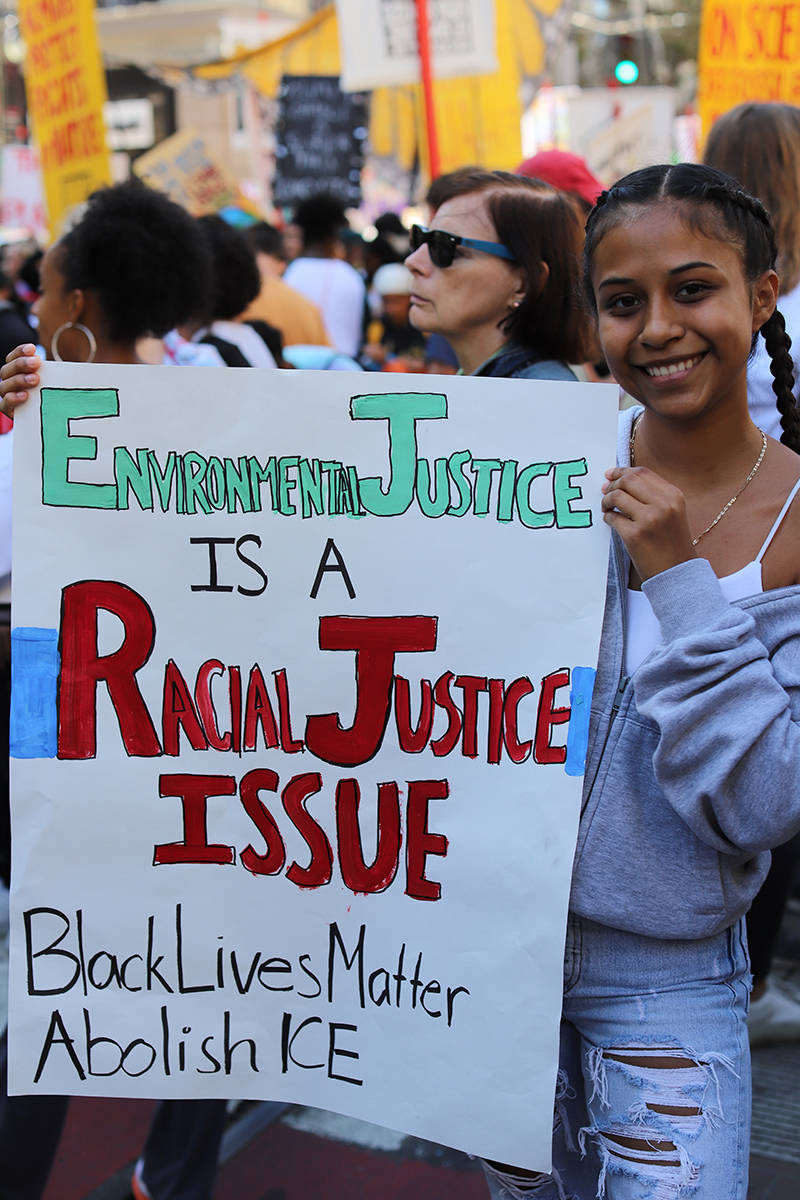 "Demonstrators at the Climate Strike in San Francisco on Sept. 20, 2019. A teenage girl holds a sign that says ""Environmental racial justice issue. Black Lives Matter. Abolish ICE."""
