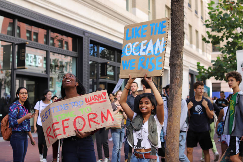 "Demonstrators at the Climate Strike in San Francisco on Sept. 20, 2019. One holds a sign that says ""Like the ocean we rise."""