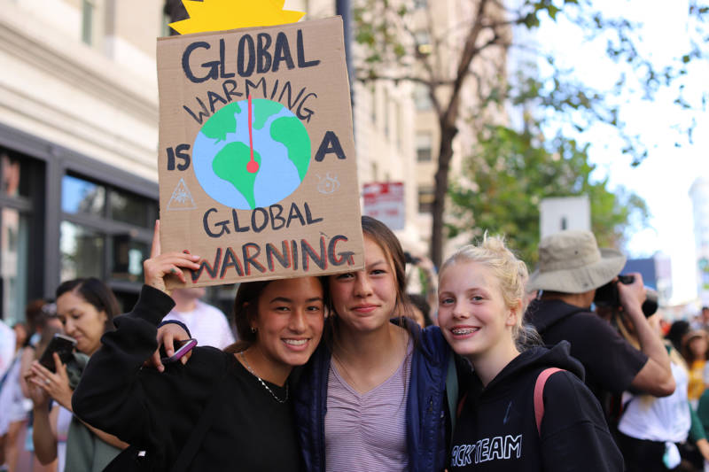 "Demonstrators at the Climate Strike in San Francisco on Sept. 20, 2019. Three teenage girls hold a sign that says ""Global warming is a global warning."""