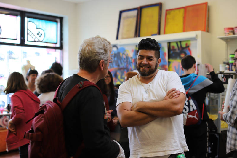 Music instructor Alfie Macias talks to a parent at X Space.