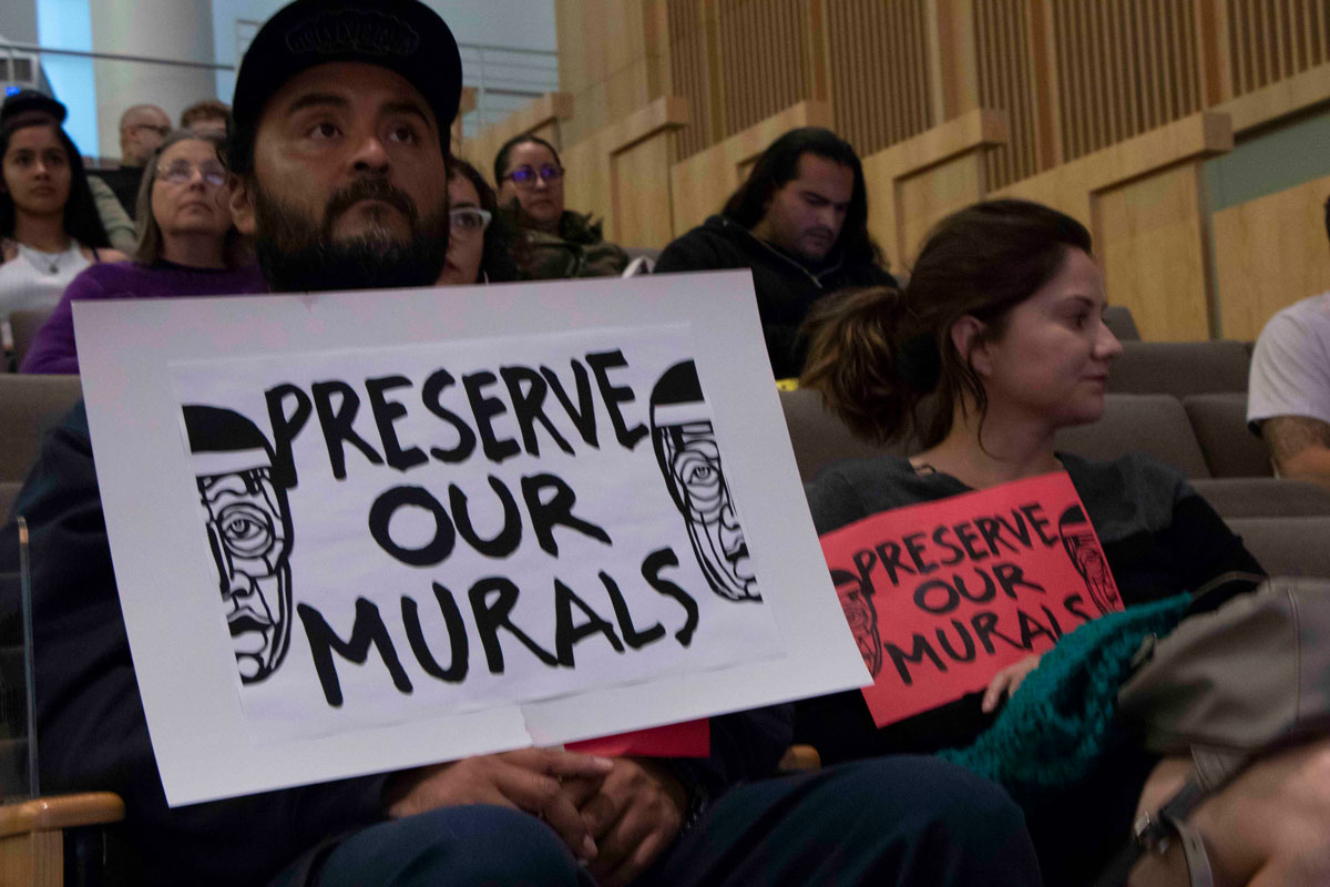 Residents Juan Carlos Araujo and Maricela Lechuga hold up signs urging the Historic Landmarks Commission to help protect Chicano murals at City Hall in San Jose, on Oct. 2, 2019.