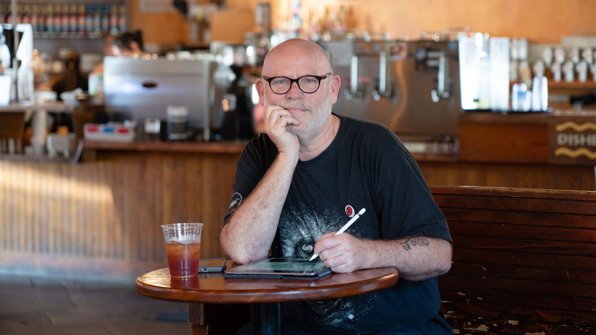 "Cartoonist Tom Beland at Aroma Roasters in Santa Rosa. Beland considers the $300 he spends every month at Santa Rosa cafes ""studio rent."" Graham Holoch/KQED"