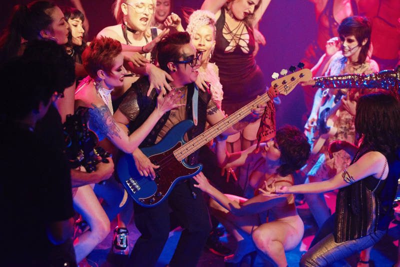 """Copyslut bassist Eli Maliwan (center) with lead singer Chatz (left) and guitarist Ray Zamora (far right) and dancers on set for the """"Makers Mark"""" music video. Maliwan strums his bass, smiling, while dancers cheer him on."""