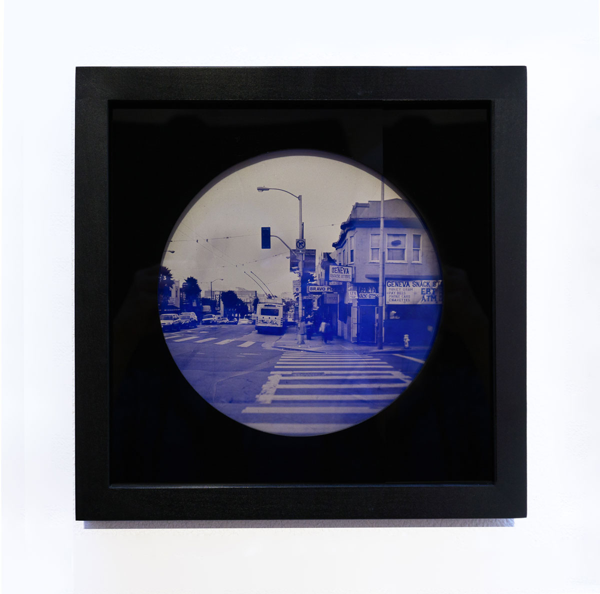 A round, blue-tinted photograph of the corer of Mission St. and Geneva Avenue in the Excelsior neighborhood of San Francisco.