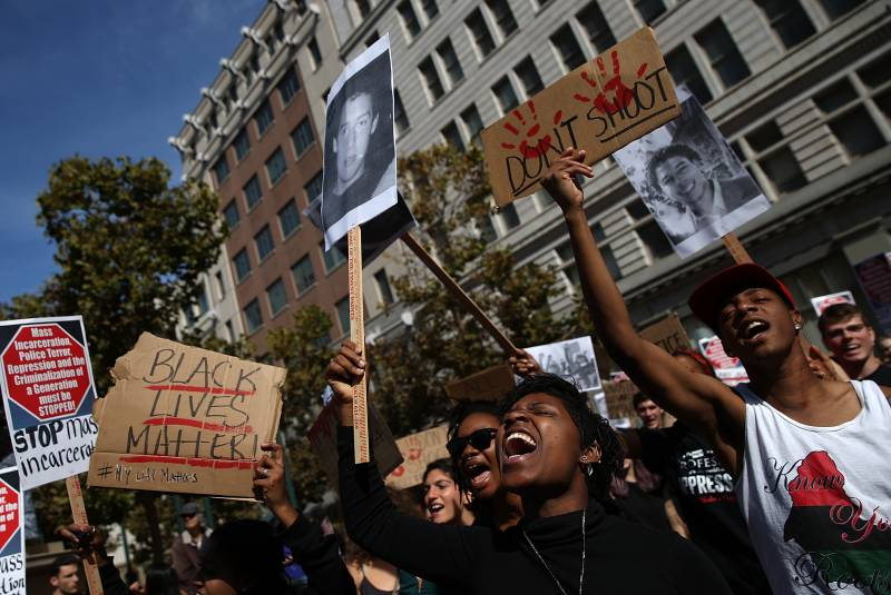 Protesters hold signs during a demonstration against police brutality on Oct. 22, 2014 in Oakland, California.