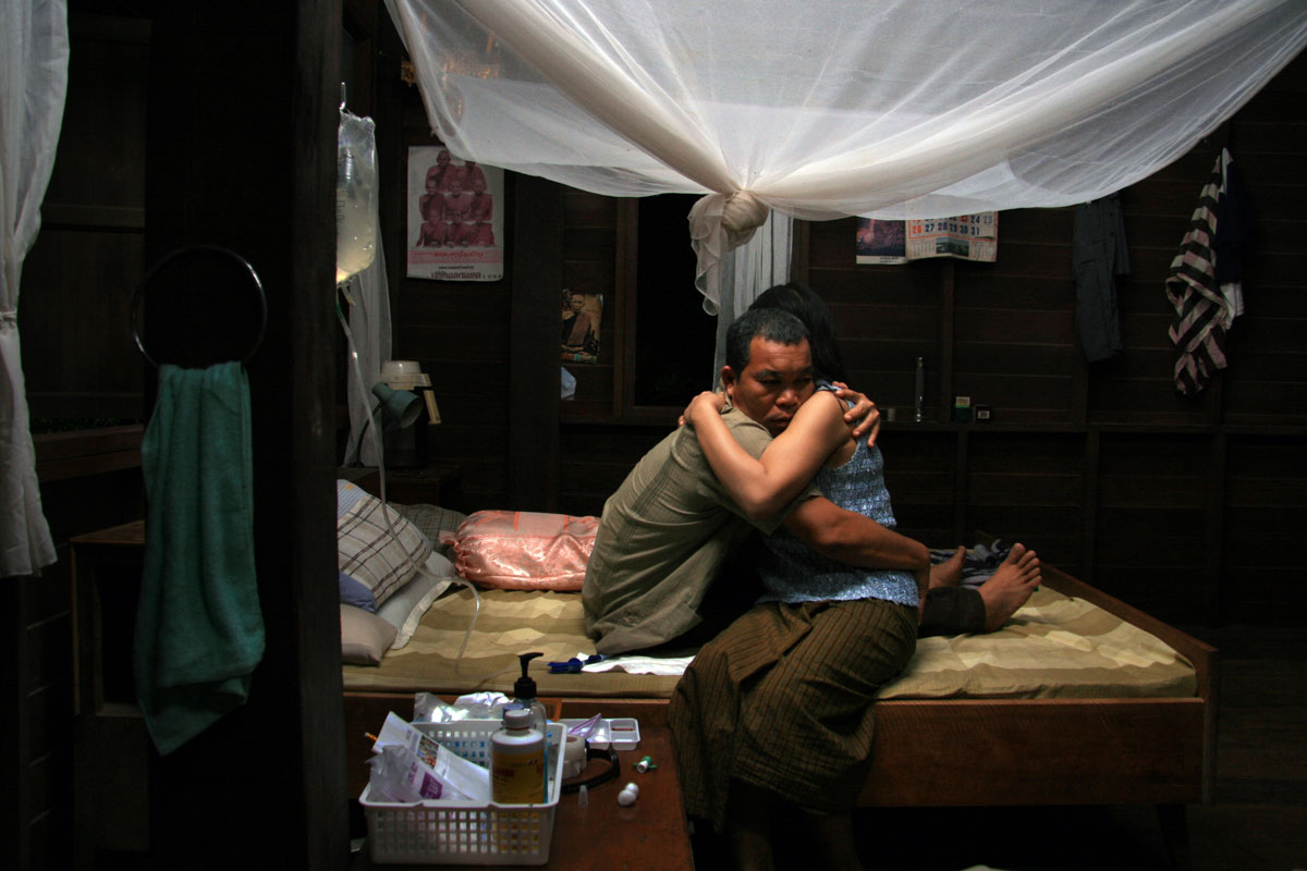 A man connected to an IV hugs a woman on a bed.