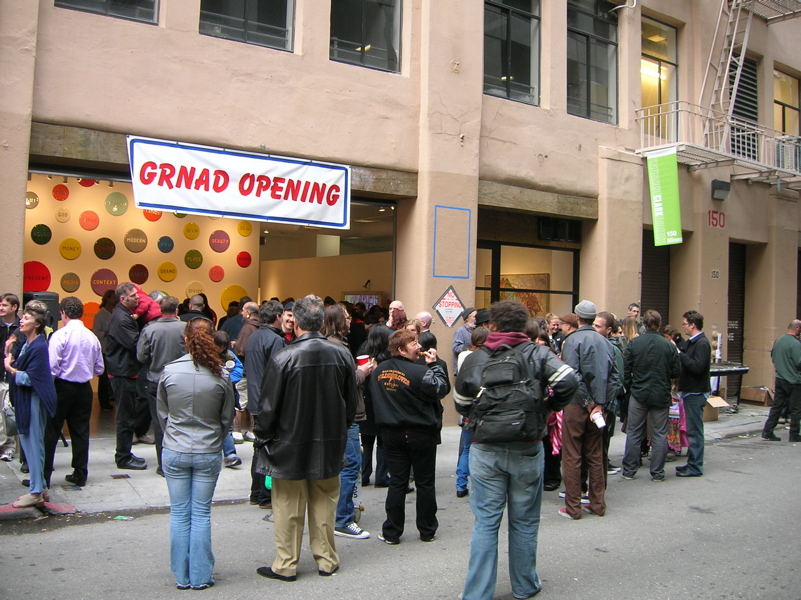 "People gathered outside the gallery on MInna Street, a banner reads ""GRNAD OPENING"" over the roll-up door."