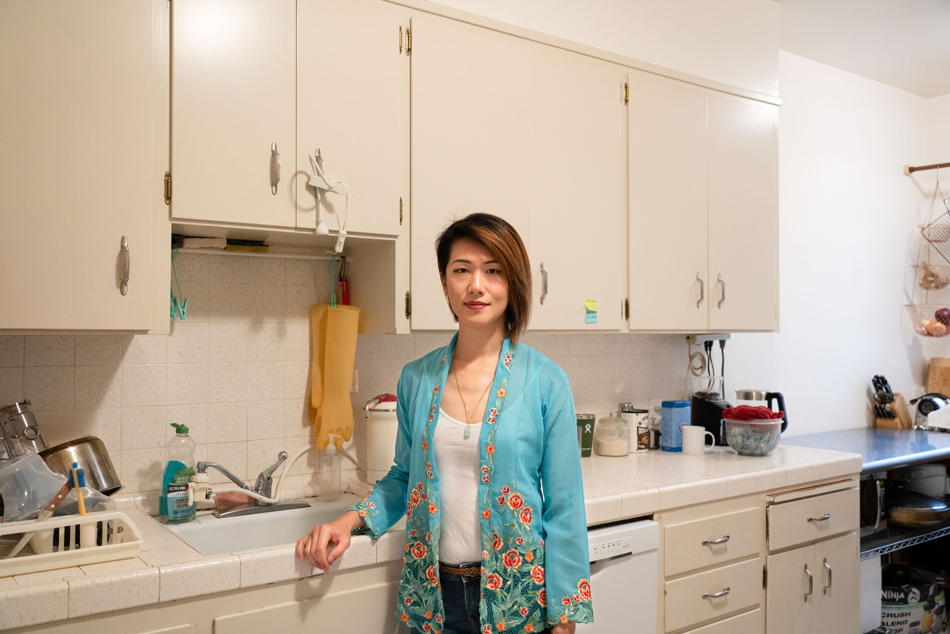 Woman in turquoise shirt leans one arm on the edge of sink, stands in her kitchen in front of cabinets and a long tiled counter.