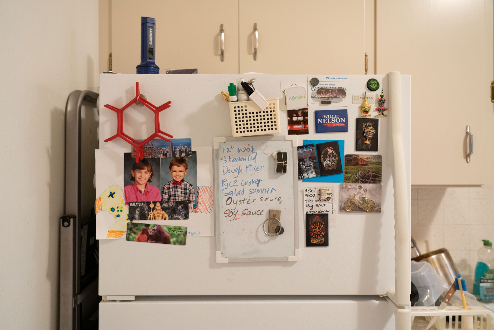 Postcards, photos, magnets and a shopping list cover the freezer door of a white refrigerator.