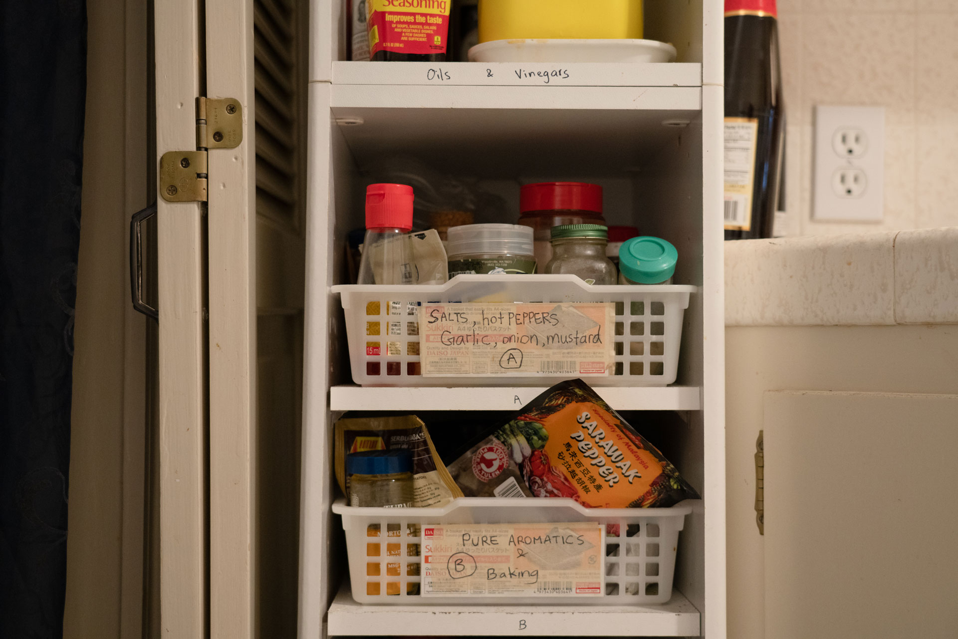 Labeled baskets of spices sit in a white shelf in the kitchen.
