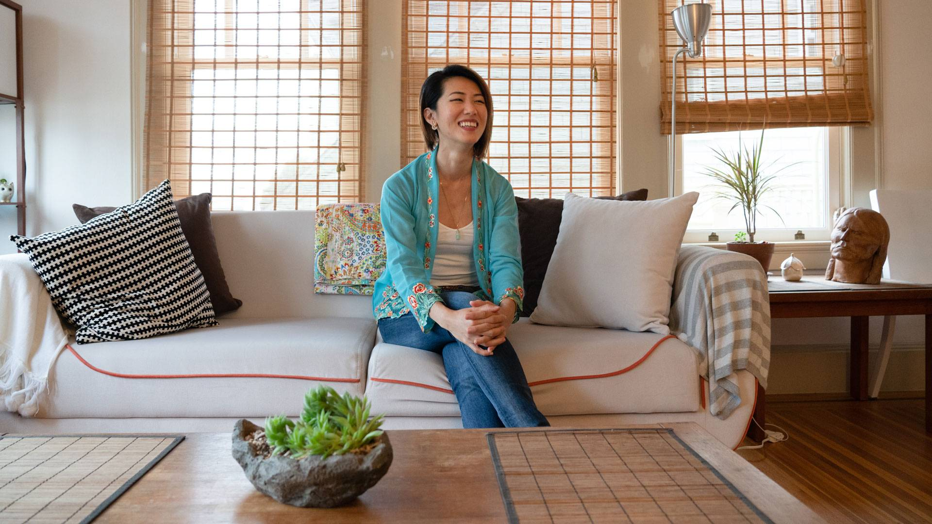 Tracy Goh at home in her Sea Cliff apartment, on the couch that doubles as her office.  Graham Holoch/KQED